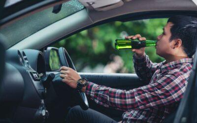 mężczyzna pije piwo za kierownicą auta