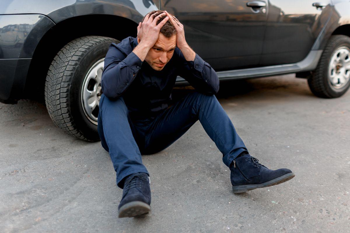 załamany mężczyzna siedzi oparty o koło auta